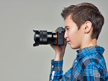 Boy with photo camera taking pictures. Teen boy  with dslr camera photographing. Profile portrait Stock Photos