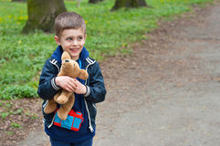Boy photographer holds toy puppy. Four year old boy cuddles toy puppy. Boy is on the road in the park. Season - spring Royalty Free Stock Images
