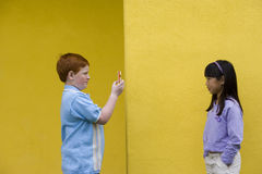 Boy (9-11) photographing girl (9-11) with camera phone beside yellow wall, profile Royalty Free Stock Photo