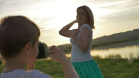 Boy photographing his mother standing on the shore of the lake in the evening at sunset stock video footage