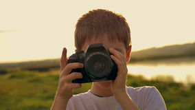 Boy photographing his mother standing on the shore of the lake in the evening at sunset stock video