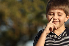 Boy picking nose. Young child smiling and picking his nose Stock Photography