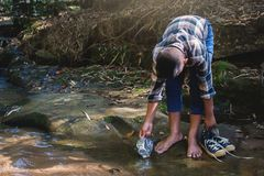 Boy picking up plastic garbage in forest Stock Photo