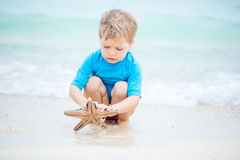 Boy picking up starfish and watching it in shallow sea water Stock Image