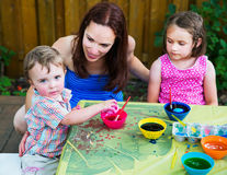 Boy Picks Up his New Dyed Pink Easter Egg. A family picture of children painting and decorating eggs.  A mother smiles at her boy as he picks up his new dyed Stock Images