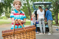 Boy with picnic basket while family in background at car trunk Stock Photos