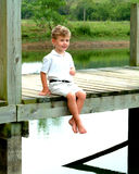 Boy on Pier. Boy sitting on pier looking toward camera on cloudy day Stock Image
