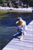 Boy on Pier. Boy sitting and relaxing on a dock while fishing in sunny South Florida royalty free stock image