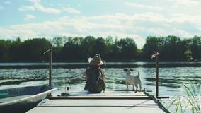 Boy on a pier with dog. Young happy boy on wooden landing stage with small dog stock footage