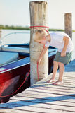 Boy on the pier with motorboat, sunny summer Royalty Free Stock Images