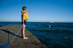 Boy on the pier waving Stock Image