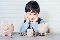 Boy with pig piggy bank Stock Photos