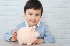 Boy with pig piggy bank. childhood, money, investment and happy people concept stock photography