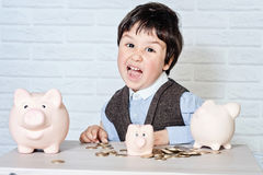 Boy with pig piggy bank Stock Images