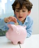 Boy piggy bank. Young boy inserting a coin in a piggy bank Royalty Free Stock Photos
