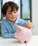 Boy piggy bank. Young boy inserting a coin in a piggy bank Stock Images