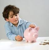 Boy piggy bank. Boy inserting a coin in a piggy bank Stock Image