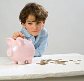 Boy piggy bank. Boy inserting a coin in a piggy bank Royalty Free Stock Image