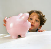 Boy piggy bank. Young boy reaching a piggy bank Stock Photography