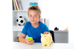 Boy with piggy-bank and phone Stock Image