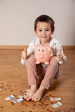 Boy with a piggy bank showing ok Stock Photo