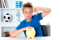 Boy with piggy-bank and thumb down Stock Image