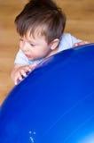Boy with pilates ball. Little boy standing next to a blue pilates ball stock photo