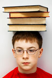 Boy with a pile of books. On her head Stock Photo