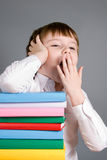 Boy with a pile of books yawns Royalty Free Stock Photos