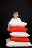 Boy with pile of cushions Stock Images