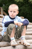 Boy on pile of logs. Young boy sitting on pile of logs with unhappy expression stock image