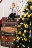 Boy on pile of suitcases at christmas tree. Little boy on pile of suitcases at christmas tree with big clock indoors Royalty Free Stock Photography