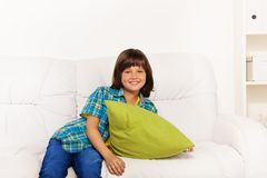 Boy with pillow on a coach. One happy calm and relaxed little boy 6 years old sitting with green pillow on the white leather coach in living room at home Stock Images
