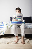 Boy with pillow looking sideways. Caucasian brunette boy with pillow sitting on the bed looking sideways Stock Images