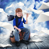 Boy Pilot with Paper Airplanes Flying in Sky. A little child is holding a paper airplane in the sky dreaming about being a pilot flying. The boy is happy for a Stock Photography