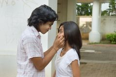 Boy pinching girl's cheeks. Two teenage lovers of mixed ethnicity standing in front of each other in a lofty patio, boy pinching cheeks of girl in a tender way Stock Images