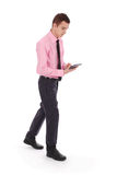 The boy in a pink shirt goes holding tablet PC Stock Images