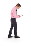 The boy in a pink shirt goes holding tablet PC Stock Photo