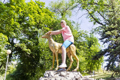 Boy in pink shirt sitting on a golden goat Stock Images