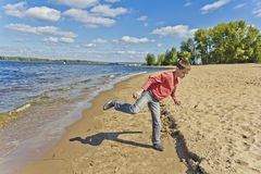 Boy in pink are throwing sand on a beach Royalty Free Stock Photos