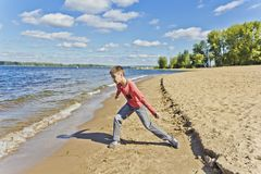 Boy in pink are throwing sand on a beach royalty free stock images