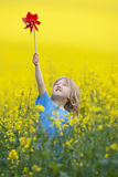 Boy with pinwheel. Boy with long blond hair holding pinwheel in canola field Stock Photography