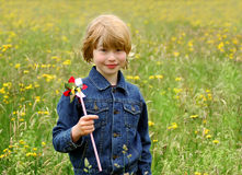 Boy with pinwheel. Cute blond boy having fun with pinwheel in meadow Royalty Free Stock Photos