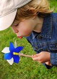 Boy and pinwheel. Cute blond boy having fun with pinwheel in meadow Royalty Free Stock Photography