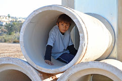 Boy In A Pipe - Sewer Drainage Drain. A boy looking out of a large drainage pipe Stock Photography