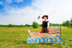 Boy in pirate hat with sword stands on carton ship Royalty Free Stock Photography
