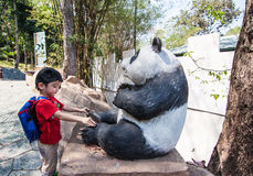 The boy is pitting around panda statue Royalty Free Stock Image