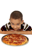 Boy and pizza. A young hispanic boy ready to eat a pepperoni pizza royalty free stock images