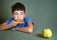 Boy with pizza refuse to eat apple. Teen handsome boy with pizza refuse to eat apple Royalty Free Stock Photos