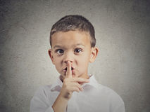 Boy placing finger on lips, quiet gesture. Closeup portrait young serious child, boy placing finger on lips as if to say, shhh, be quiet, silence, isolated grey stock images